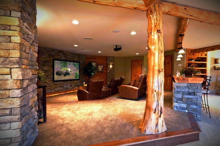 Comfortable entertainment room with theater seating in the for Rustic finished basement
