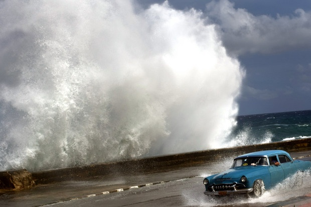 A driver maneuvers his classic American car along a wet road as a wave crashes against the Malecon in Havana, Cuba, on Oct. 25, 2012. Hurricane Sandy blasted across eastern Cuba on Thursday as a potent Category 2 storm and headed for the Bahamas after causing at least two deaths in the Caribbean.