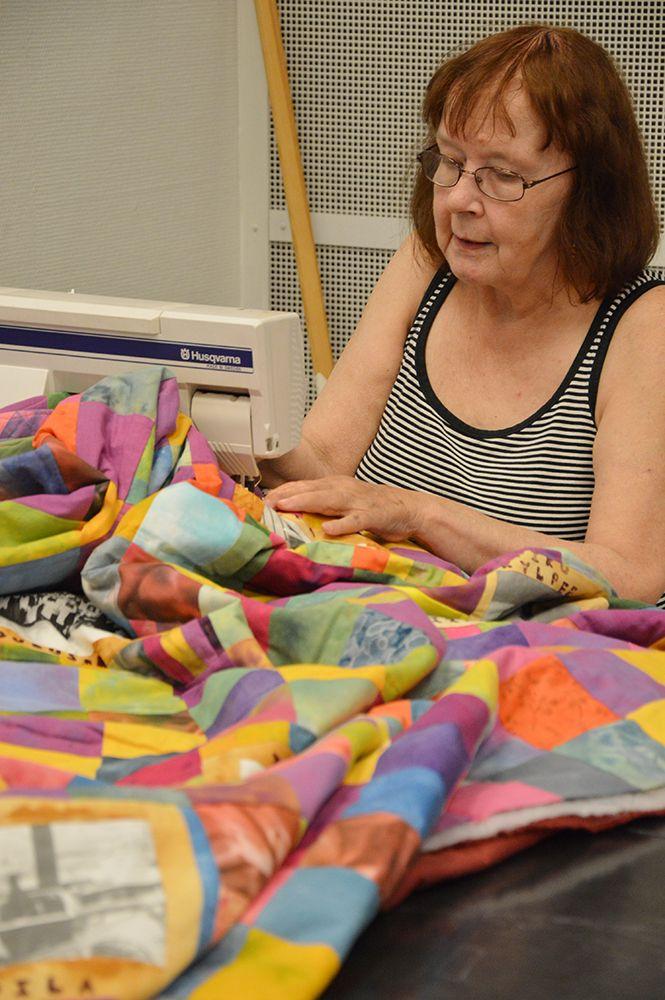 Vuokka Isaksson ompelee värikästä tilkkuteosta taidemuseolla Taiteiden yönä. Luuppi, Oulu (Finland)