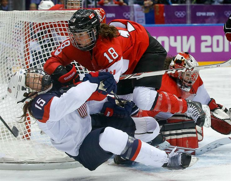Catherine Ward of Canada, top, shoves Anne Schleper of the United States to the ice during overtime of the women's gold medal ice hockey game at the 2014 Winter Olympics on Feb. 20, in Sochi, Russia.