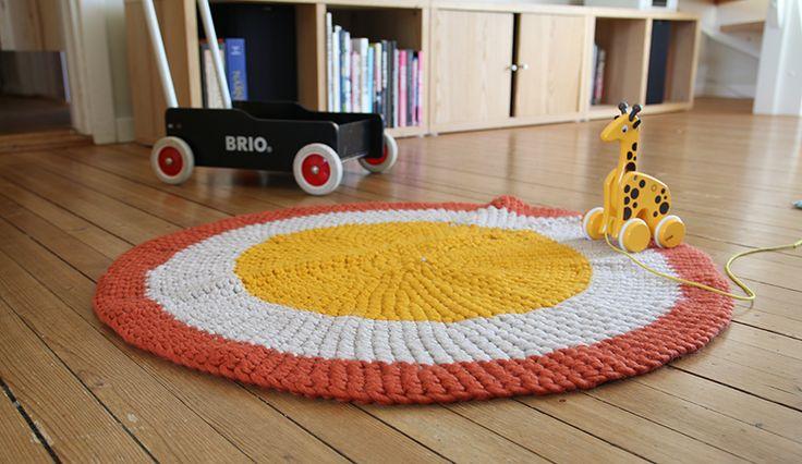 Heklet, rundt teppe i flere farger. Fint å se på og holder stumpen varm under lek på gulvet.