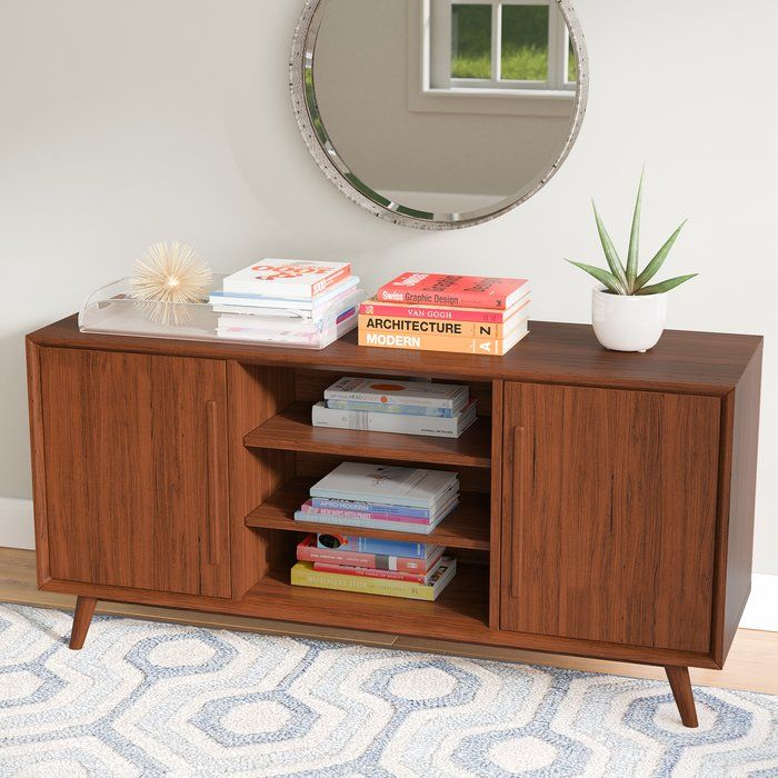 With a design that would look right at home in a 1950's American suburban home or in a 2010's luxury apartment, this chic TV stand will bring midcentury appeal and modern flair to your space. The tapered, angled legs offer an attractive vintage look while the wood grain details add just a touch of pattern. More than just stylish, it also features an open center with two adjustable shelves perfect for media accessories and decorative items alike. The two side cabinets with adjustable shelves…