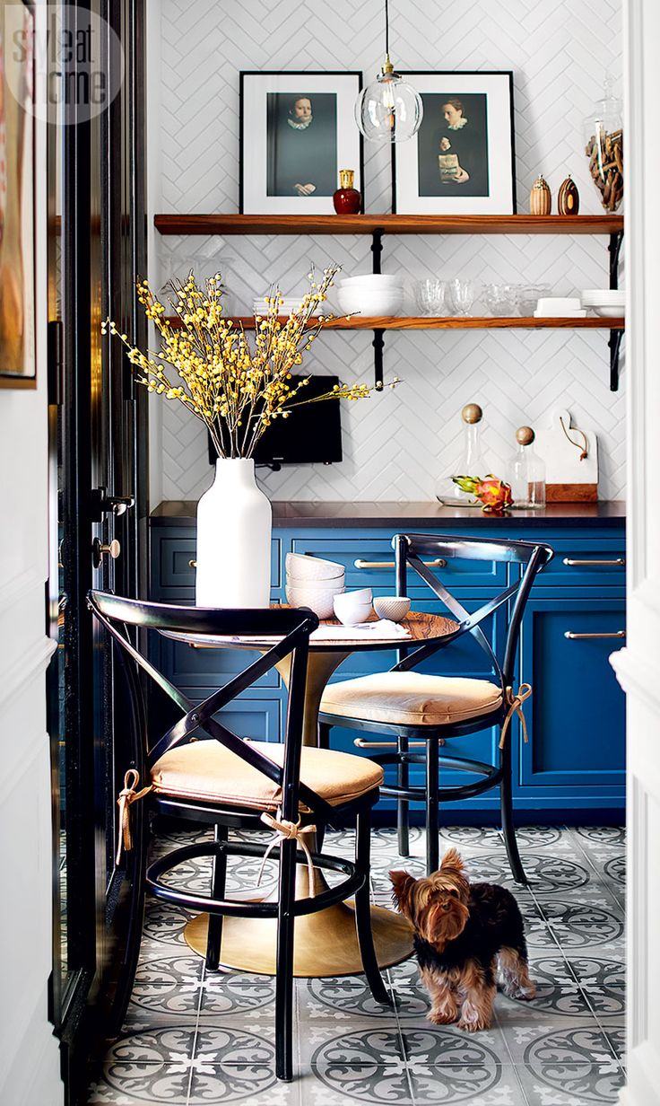 """""""I said, 'let's do a non-kitchen – one that looks like an open bistro, where you are not oppressed by upper cabinets but instead are surrounded with beautiful objects and art,"""" says Philippe. """"And that's exactly what we did."""" (Romeo, the couple's Yorkshire terrier, takes a moment to consider the renovation.)"""