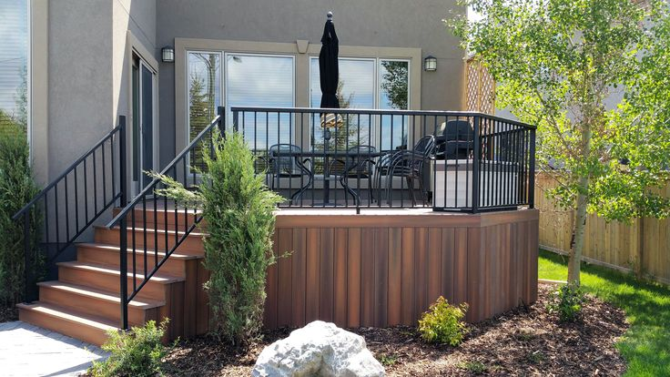 CREATE ESCAPE - Wentworth.  Ipe - Fiberon Horizon deck with black aluminum railing. New trees and shrubs that soften the look. Lots of usable space for your family and guests.