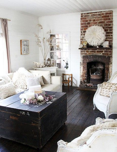 Shabby chic. Bare brick chimney. Dark wood floorboards. White walls and sofas. Vintage chest.