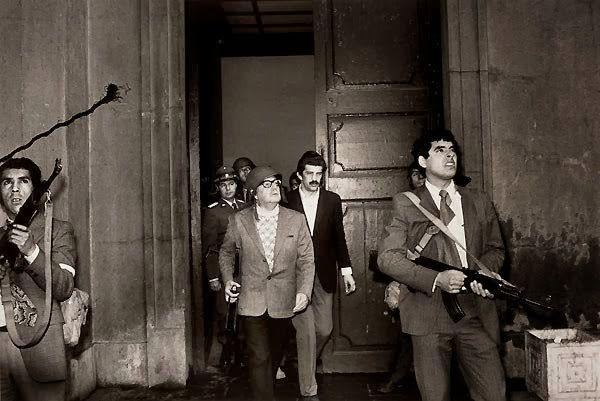 1973 yılında Şili'de demokratik seçimle gelen Başkan Salvador Allende'nin askeri darbe sırasında ölümünden birkaç saniye öncesi. Fotoğrafı çeken kişinin 'kişisel güvenliği' için adının açıklanmasını istemediği sanılıyor.