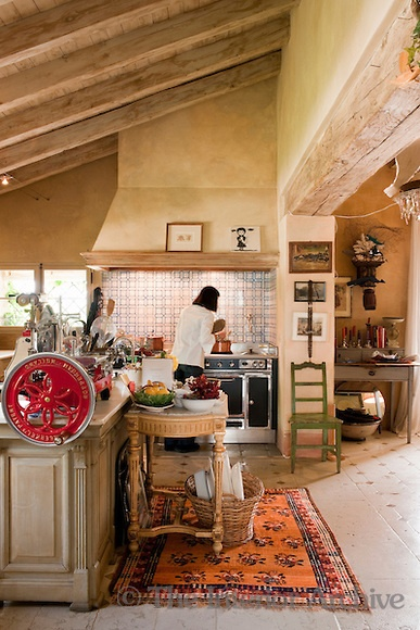 Kitchen of Maddalena Caruso - A bright red vintage meat slicer sitting on the kitchen island unit is one of the many eclectic pieces that gives this large country kitchen personality as well as functionality