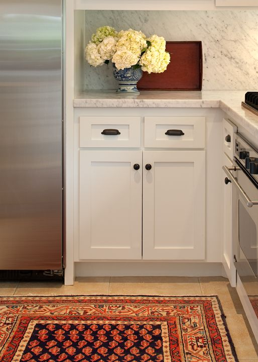 white cabinets and carrara marble stainless steel appliances and Persian runner