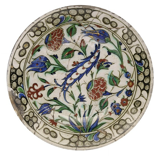 AN IZNIK POTTERY DISH   OTTOMAN TURKEY, EARLY 17TH CENTURY   On short foot, the bole-red, cobalt-blue, sage green and black decoration with gold highlights, a saz leaf in the centre