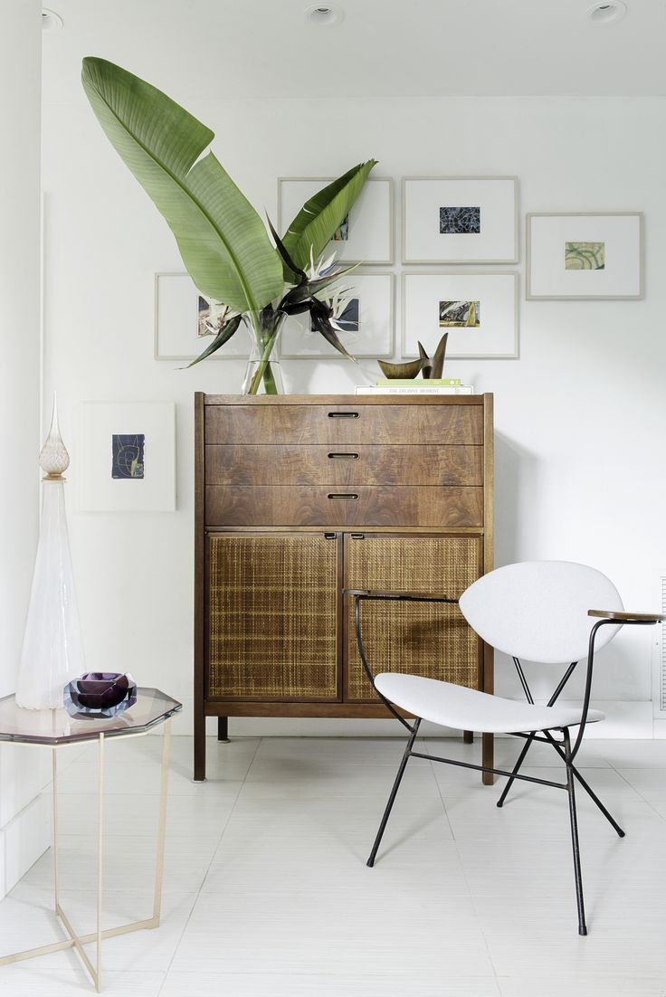 Beautiful nook with vintage style dresser, unusual gallery wall art placement, modern chair and relaxed uncluttered vibe