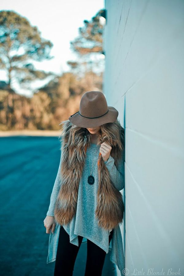 how to wear a fur vest | The perfect simple fall outfit consists of a huge sweater, a fur vest, and a floppy hat.: