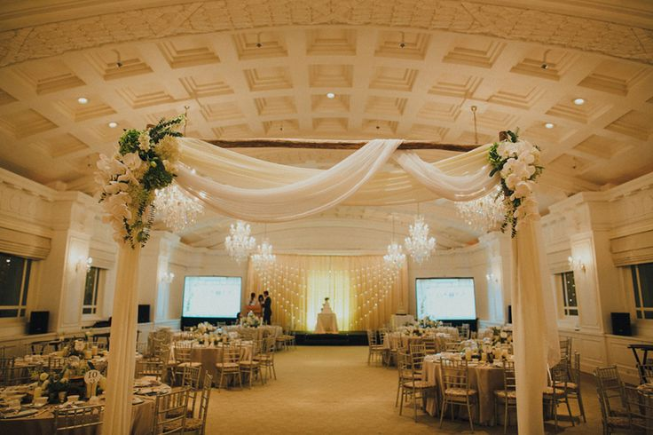 Wedding ceremony floral arch of white drapery and white flowers // Ivan and Vanessa's Rustic Moss and Terrarium Wedding at The Straits Room