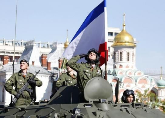 A Russian serviceman aboard an armoured personnel carrier salutes next to the blue-white-red tricolour flag of Crimea, during the Victory Day parade in Moscow's Red Square May 9, 2014. Russia celebrates the 1945 victory over Nazi Germany during World War Two on May 9. REUTERS/Grigory Dukor