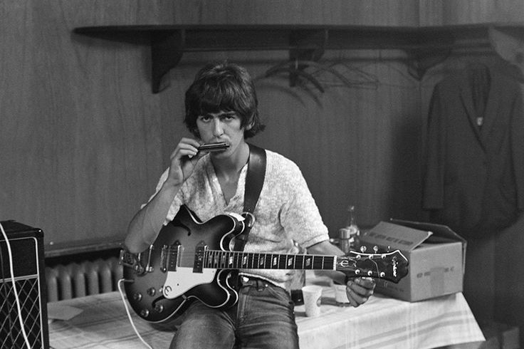 16AUG1966 George backstage at Philadelphia's JFK Stadium, using a harmonica to tune his Epiphone Casino.
