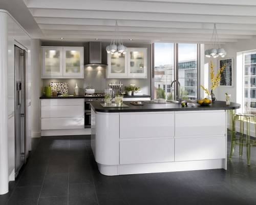 Gloss White Integrated Handle - A gloss white door with an integrated linear pull handle. Team with curved units and decorative accessories to creat an attractive feature. Add matching blackstone worktop and flooring to complete this stylish, minimalist kitchen.