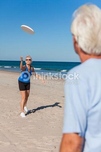 Stock Photo : Healthy Senior Man Woman Couple Playing Beach Frisbee