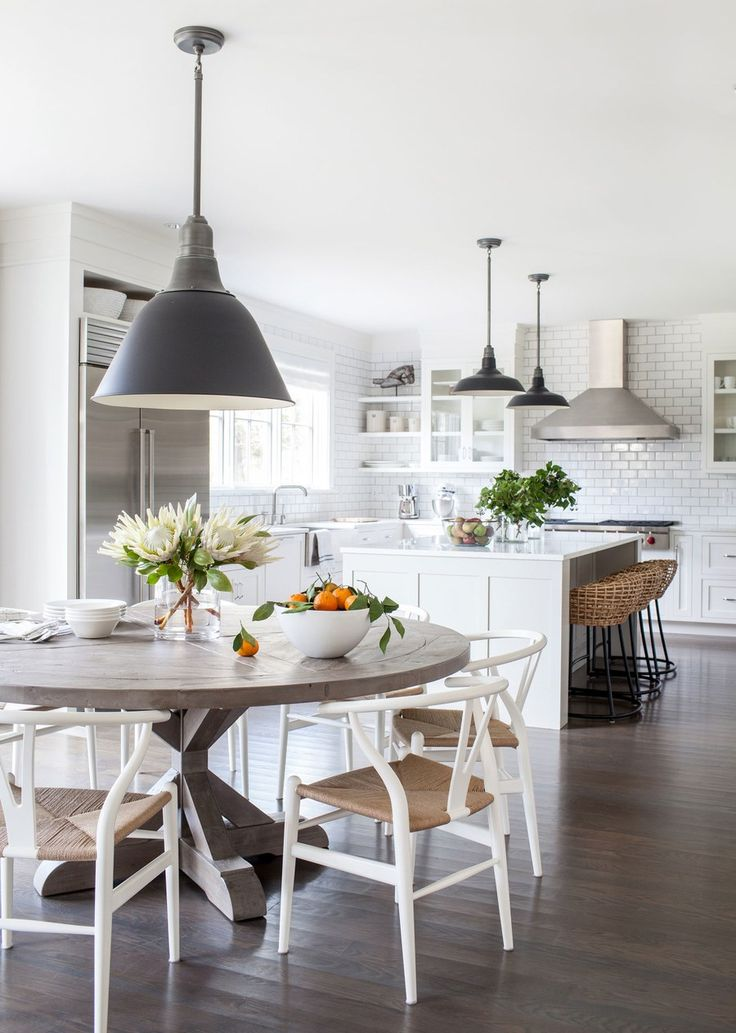 To balance out the glossy all-white kitchen, Simonpietri brought in warm woven barstools from Palecek, a round salvaged-wood dining table from RH, and Wishbone chairs by Hans J. Wegner from Design Within Reach.