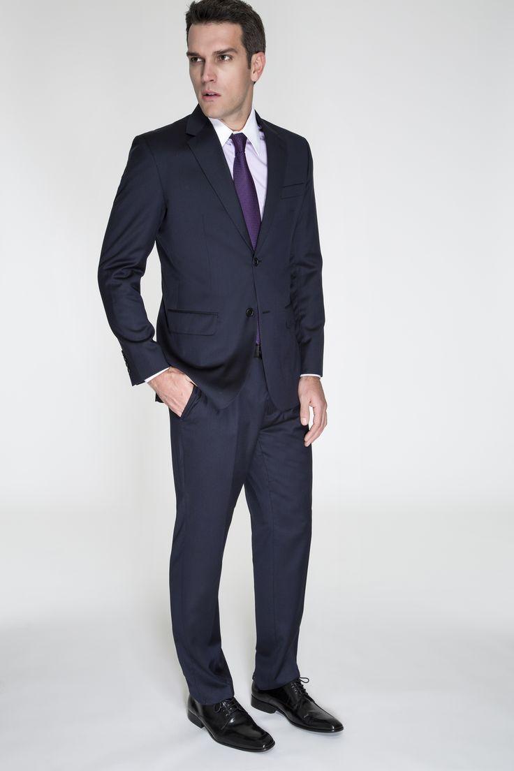 Costume azul marinho com camisa lilás listrada com colarinho branco e gravata roxa.