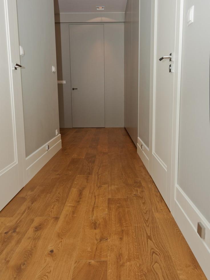 Korytarz w wydaniu nowoczesnym, a zarazem klasycznym - białe drzwi i listwy przypodłogowe, szare ściany i drewniana podłoga