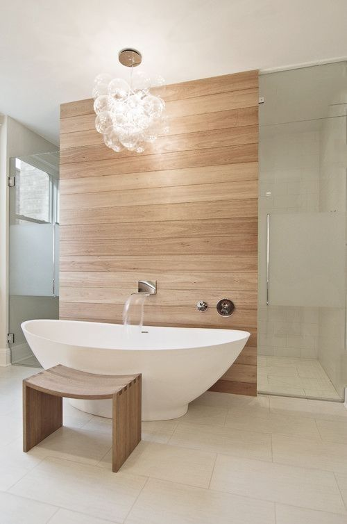 Interesting layout. Like the floor tiles, the light fitting, the tub and the tap but might prefer darker wood