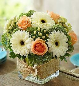 """Modern Rose and Gerbera Daisy Bouquet """"This design stirs up feelings of peace and tranquility."""" The arrangement features roses, gerbera daisies, hypericum and a garden variety of greenery in a cube va"""