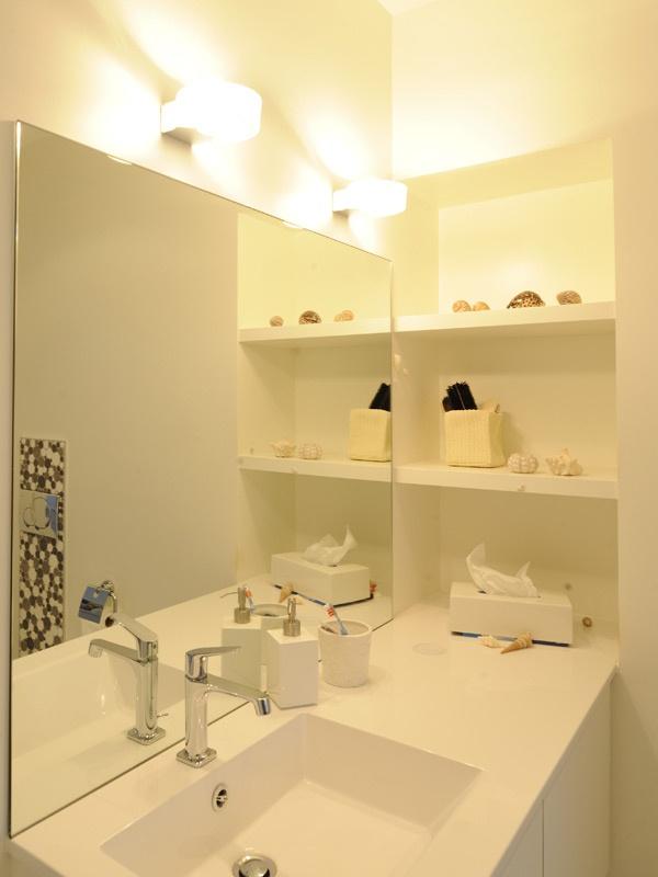 Détail de salle de bains - Plan de toilette en corian et applique Artemide