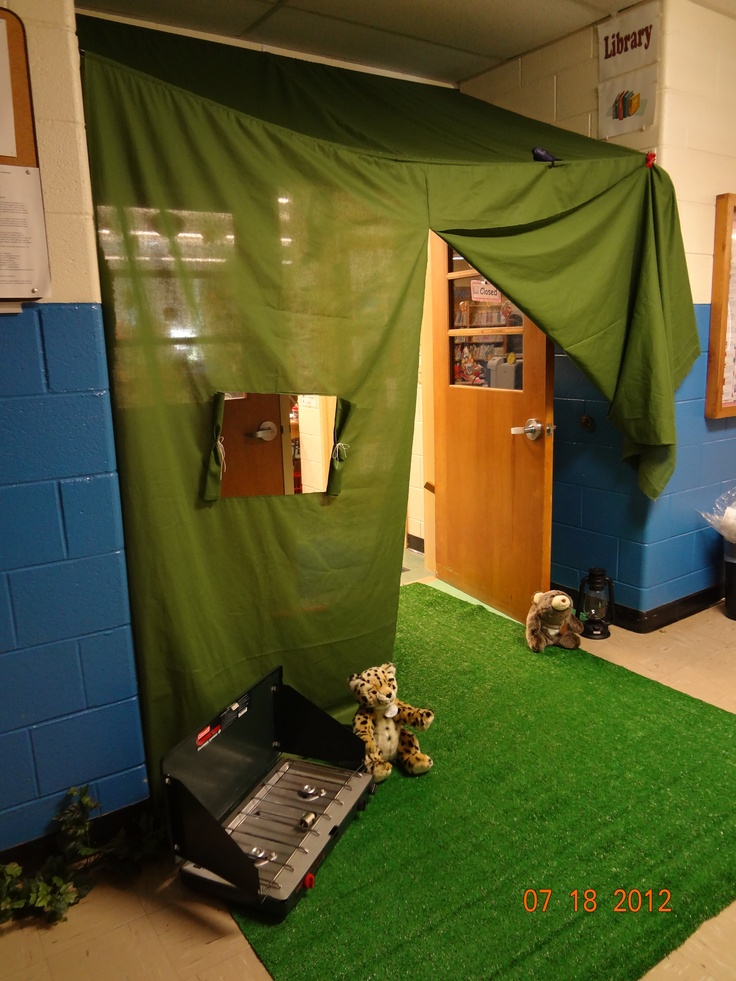 """I used Pinterest ideas to create a """"tent"""" outside the library for summer school.  I used two lengths of 45"""" wide cotton/poly and sewed them partly together.  Then I folded and sewed a rod pocket at the top and a second one with ribbon 50"""" down.  I added a netting window and used tension rods to hold them between the walls."""