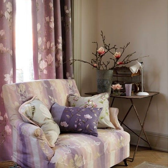 Relaxed seating area with armchair and cushions, full-length curtains and side table.