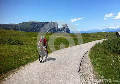 A male cyclist riding along a tarmac path in Italian Dolimites (Alpe di Siusi) with The Sciliar (Schlern) mountain range in the background.