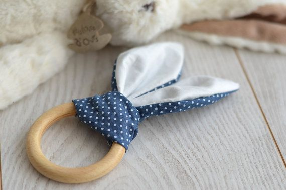 Teether. Teething rabbit to Sleigh bells ring. Colours white and blue with white polka dots.  Cotton bunny ears. Ring wood 7 cm in diameter, that baby can