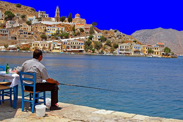Did I mention I could live here......LOVE this!! Man fishing seated at a taverna on the edge of water. Yialos, Symi island, Dodecanese, Greece