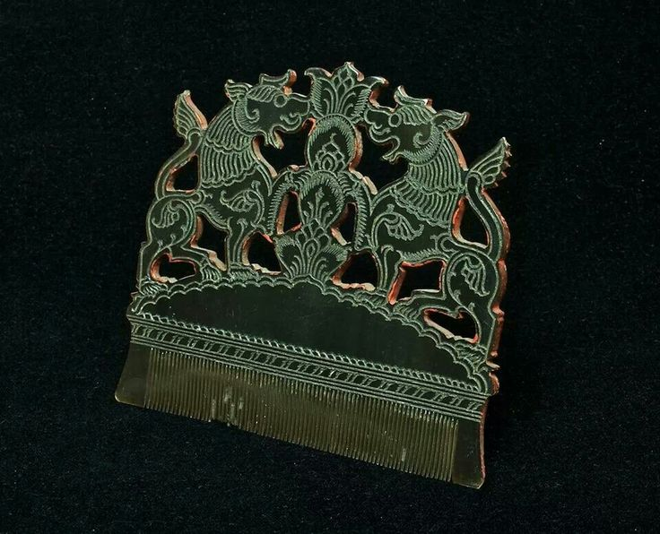 Ornamental comb depicting two mythological lions, facing each other, (Chinthe in Burma, or Rajasi in Thailand)  Burma, 19C - early 20C Water buffalo horn carved/incised on both sides, mysterious traces of silver in incised rows (?) red paint on inside and outside edges, beautifully enhancing the whole design.