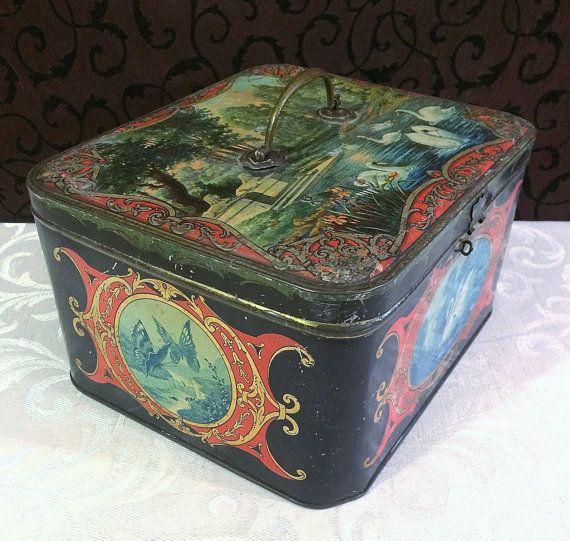 Una impresionante declaración grande con precioso arte cuenta con cisnes y mariposas, esta caja de lata antigua grande es francesa y probablemente a la década de 1910. Por favor vea la descripción completa más abajo. _____________________________________  Antiguo bellísimo cuadro, de gran tamaño de la lata y gloriosamente decorada con cisnes y mariposas. La lata tiene un fondo negro con detalles en rojo, y una escena de jardín con cisnes y esfinges aparece a todo color en la tapa. Cisnes y…