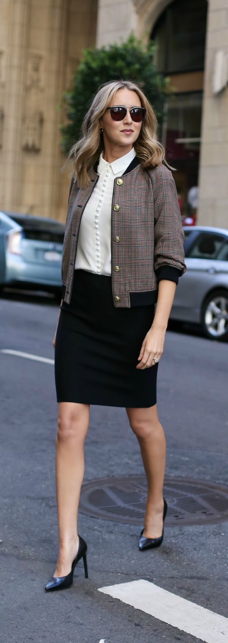 plaid bomber jacket with brass buttons, black pencil skirt, ivory victorian blouse with covered buttons, black sunglasses with gold brow bar, classic pumps