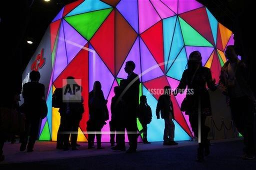 People walk by the TCL Corporation booth during the International CES, Tuesday, Jan. 6, 2015, in Las Vegas. (AP Photo/John Locher)