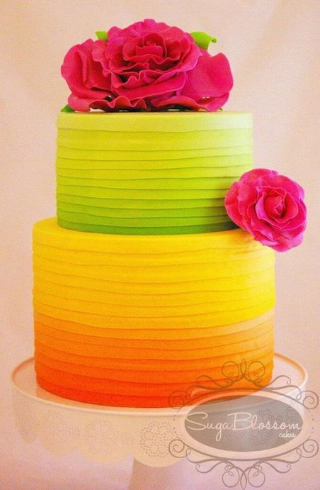 Rainbow Ombre cake in orange, yellow and green, with red flowers