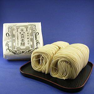 富山 大門素麺(おおおかどそうめん)JAとなみ 富山県砺波市の大門地区に伝わる郷土料理の一つ。 1848年に越中の国砺波郡大門村の住人である田守三石衛門が売薬行商で能登の蛸島を訪れたとき、前田藩の御用素麺の製法を継承し、地元に広めたのが始まり。長い麺をまるまげ状に丸めてあるのが特徴。無漂白の小麦粉、コシが強く、歯触りがよい寒造りの手延べ素麺です。