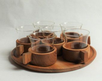 Just what your Danish modern side board has been waiting for. A set of six glass and wood coffee or tea mugs with matching tray. The wood is a lovely warm golden brown and the glass very good quality. The glasses just sit in the wooden holder so they can be easily washed separately. The tray is stamped with the Sigg logo and there is an original Sigg sticker on the bottom of one of the glasses describing them as handmade in Switzerland.  Condition: Very Good. Considering there is still a…