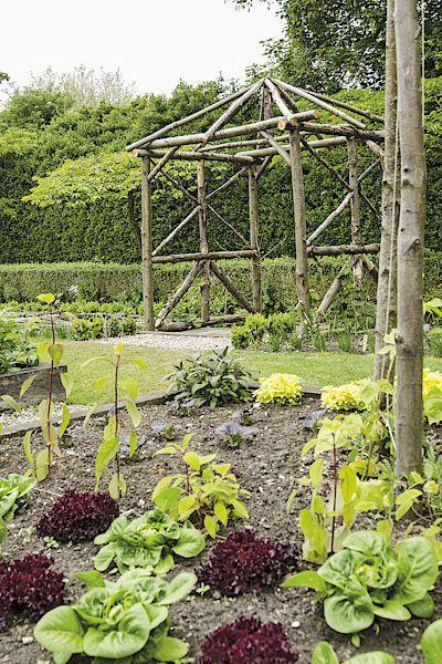 Rustikální konstrukce z kmínků stylově upozorňuje na vstup do zeleninové zahrady. Klidně se po ní můžou šplhat fazole.