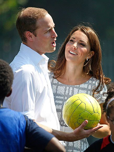 Royal Family, #Olympics2012: As his adoring wife looks on, Prince William passes on a few words to kids on the soccer field during a stop by London's Bacon School Thursday to launch Coach Core, a fitness initiative to provide training to young athletes looking to become future coaches.