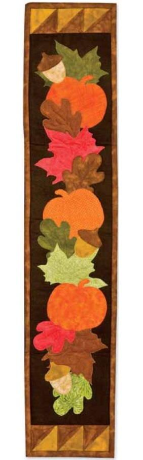 Autumn Applique Wall Hanging - This beautiful autumn quilted wall hanging pattern is the perfect project to welcome autumn in your home! The Autumn Applique Wall Hanging features applique pumpkins, oak and maple leaves, and acorns against a background of warm fall colors.