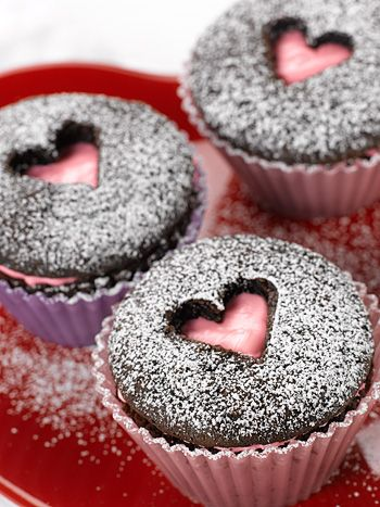Slice off top of cupcake, frost underneath, then replace top with shape cut out in middle. Sprinkle with powdered sugar