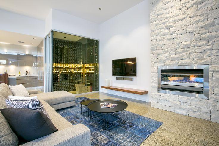 Limestone clad gas fireplace, polished concrete floor, glass wine cellar