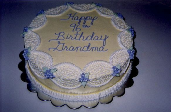 Elegant Birthday Cake for Grandmother - This cake is iced smooth in pale yellow.  White buttercream cornelli lace and small lavendar flowers accent this special cake.