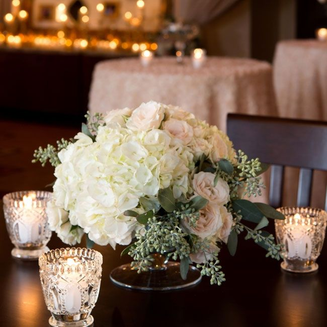 Low arrangements of hydrangeas, roses and seeded eucalyptus were surrounded by cut-crystal votive candles.