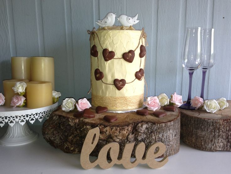 Rustic country wedding or engagement cake with love birds & chocolate hearts filled with a strawberry sauce.