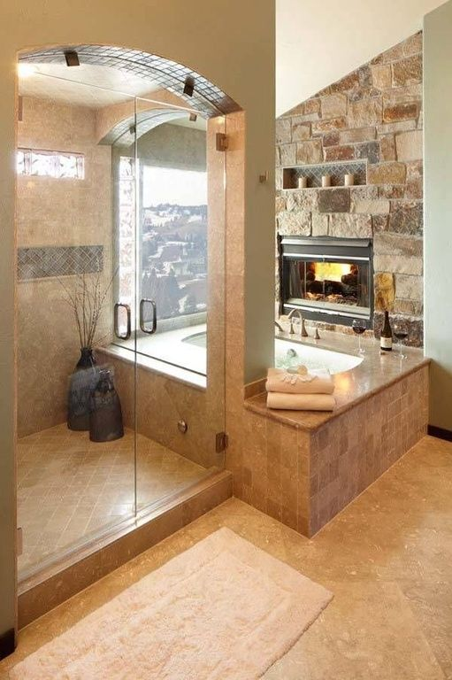 This glass enclosed shower looks over the tub and the window while a fireplace warms up the tub area. Warm hues in the tile and stone work keep this space feeling cozy despite the hard materials.
