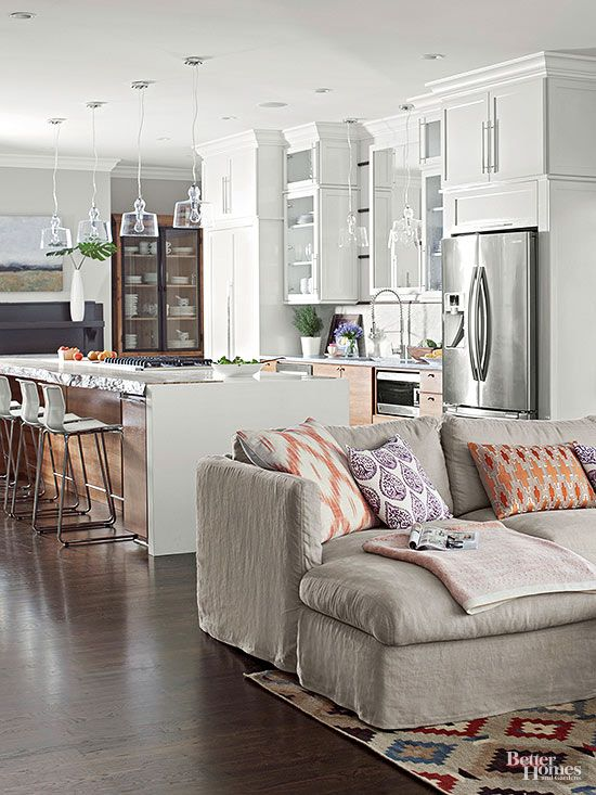 Take your cue from a kitchen's costly-to-change fittings and duplicate their colors in softer textures in an adjacent sitting area. This sofa's slightly rumpled slipcover fabric repeats the grayish tones of the streamlined appliances and stone countertops. The area rug and throw pillows echo the kitchen cabinets' ruddy undertones and black painted details./