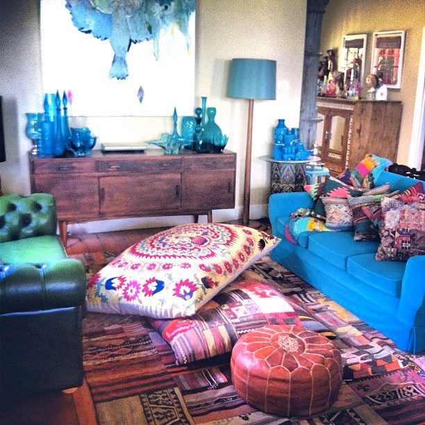 Bright comfy bohemian space. Gorgeous kilim rug, Moroccan leather pouf, Indian floor pillows and bright sofas.