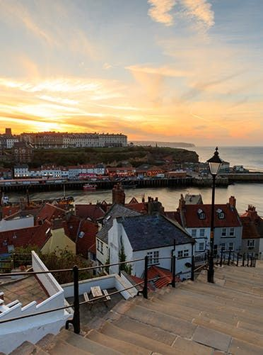 Whitby, England This picture-perfect seaside town in Yorkshire is divided by the River Esk. The most famous spot in town is known as the 199 Steps, a steep trail that leads to the scenic Whitby Abbey, the remains of a Benedictine monastery that inspired the story of Dracula.  The 15 Most Adorable Small Towns in Europe via @PureWow